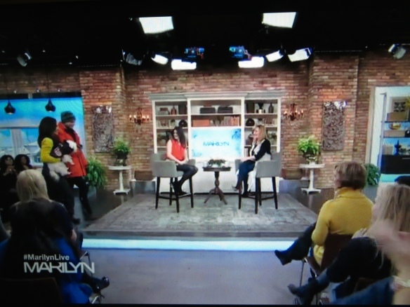 A screen shot of the show.  See me in front row!  They tell audience to wear bright, jewel-coloured clothing.  I think my bright yellow sweater helped me get this top spot because the coordinator hand-selects where everyone will sit.