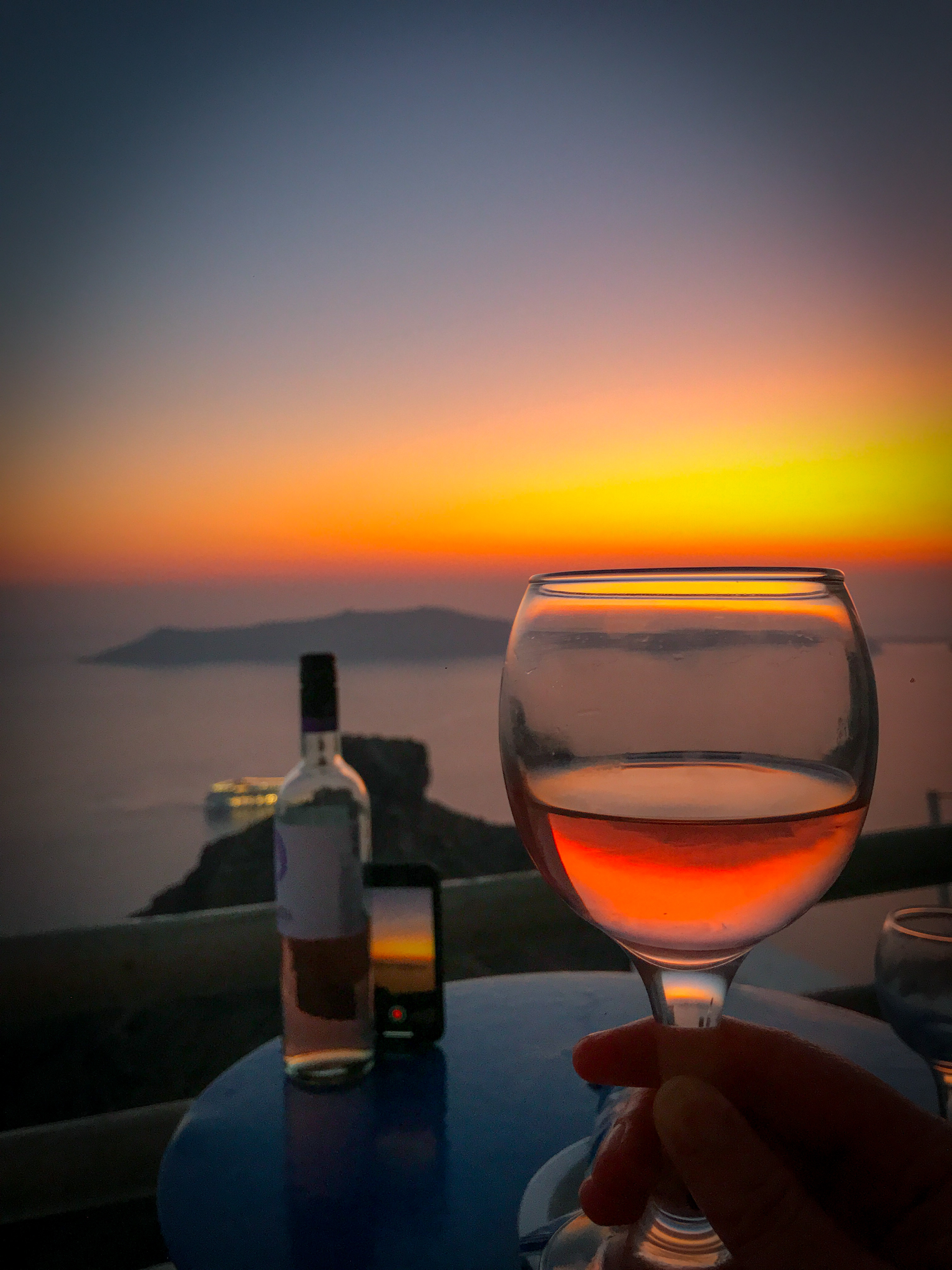 A Santorini Sunset as it reflects through a wineglass and our other phone propped up against the wine bottle as we take a time lapse of the sunset.