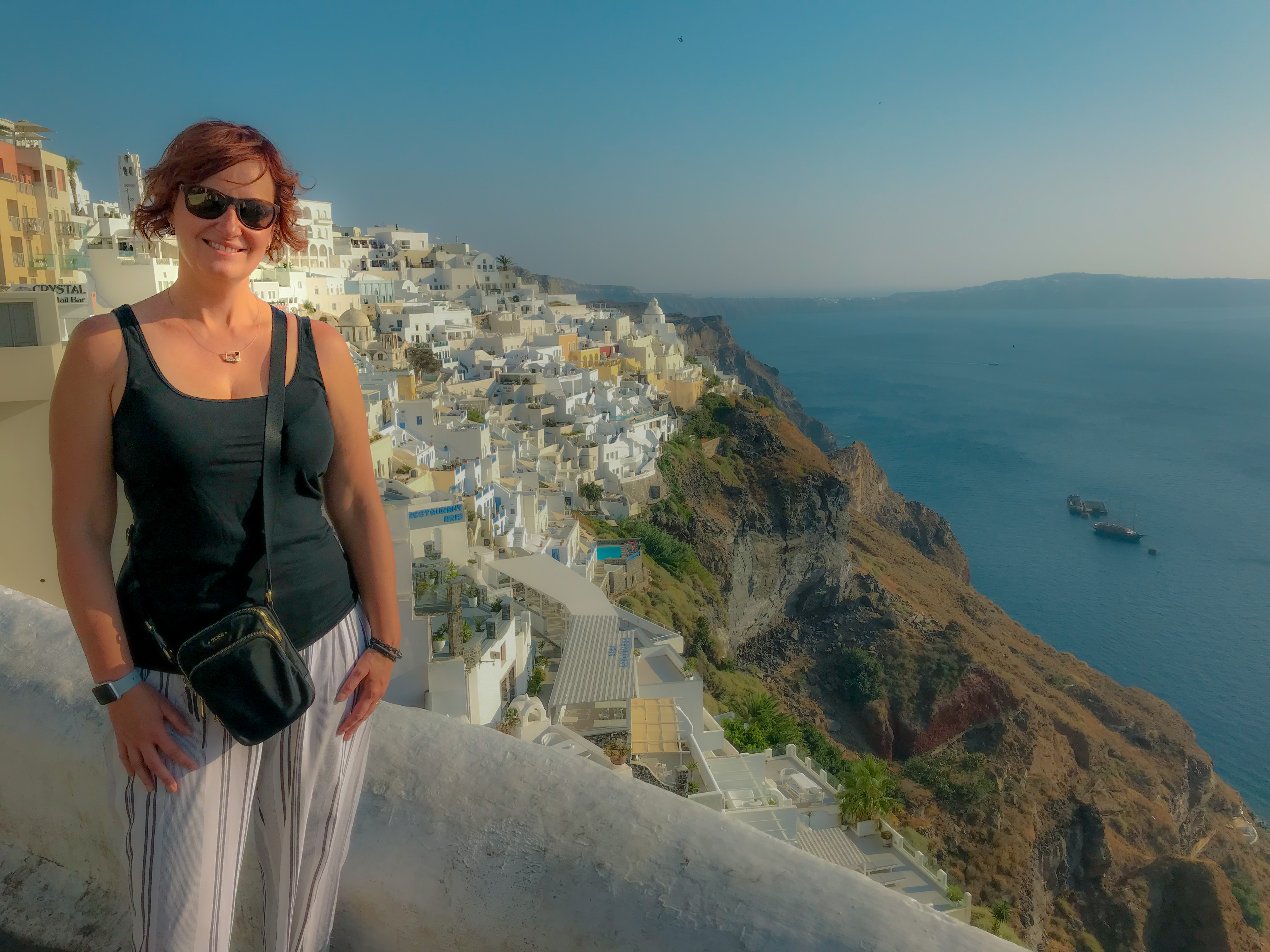 Tamara standing with a view of the whitewashed buildings on the cliffs of Santorini.