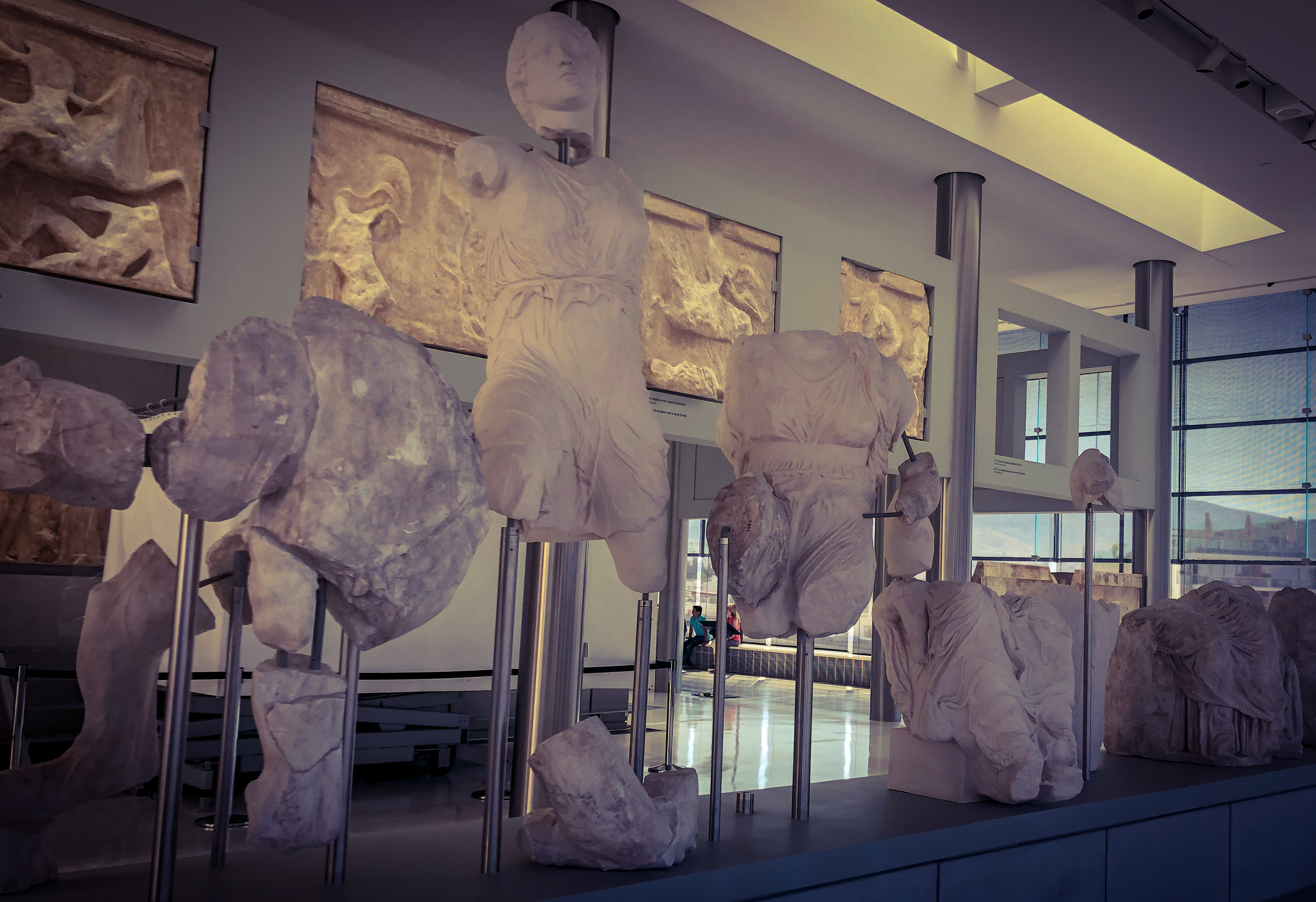 Artifacts from the Parthenon on display at the Acropolis Museum with the Parthenon seen through the window at a distance.