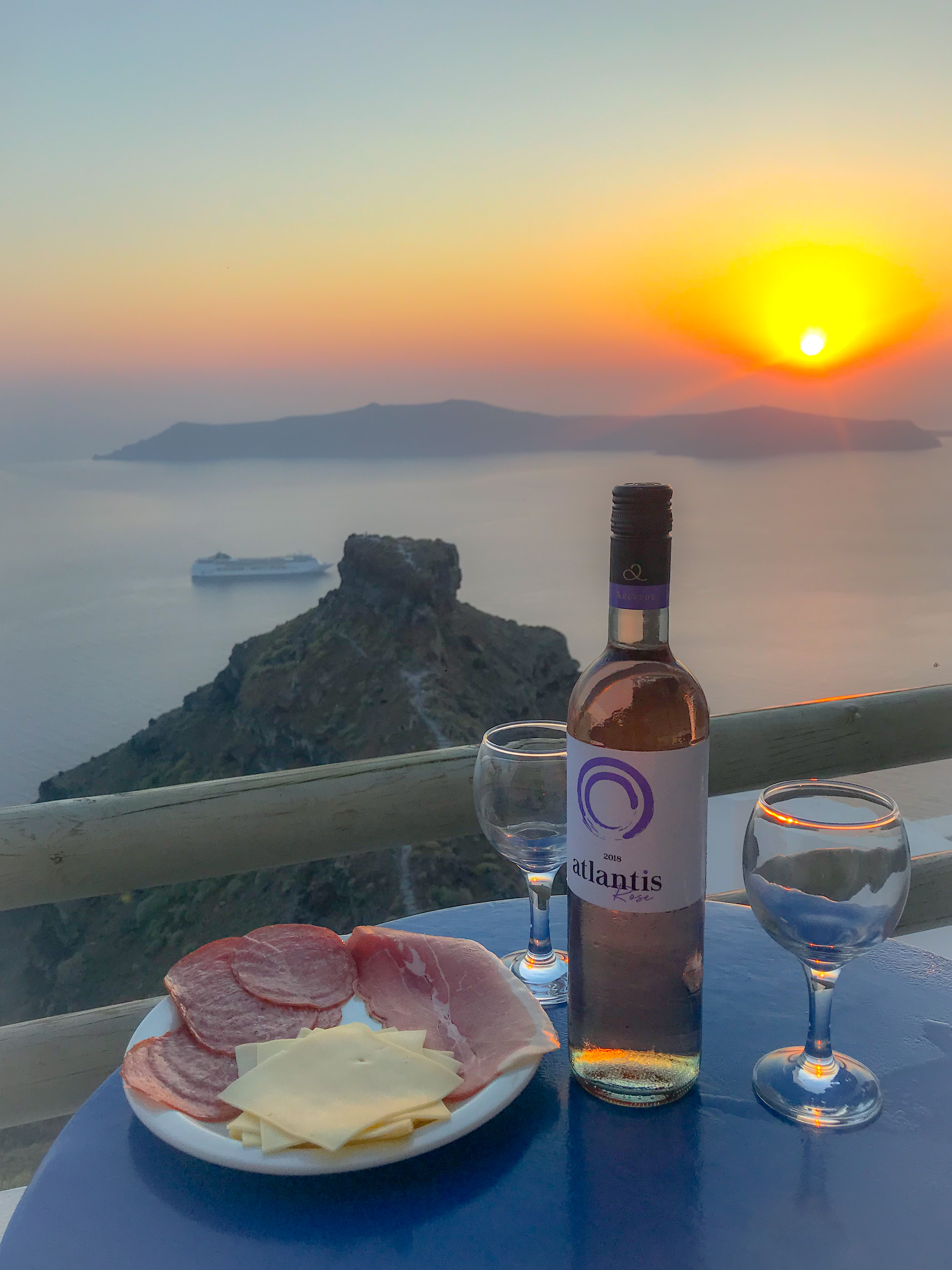 A Santorini sunset from Imerovigli with Skaros Rock in view, along with the island of Thirasia in the distance. A table with a bottle of Atlantis Rose wine, 2 wine glasses and a charcuterie plate are in the foreground.