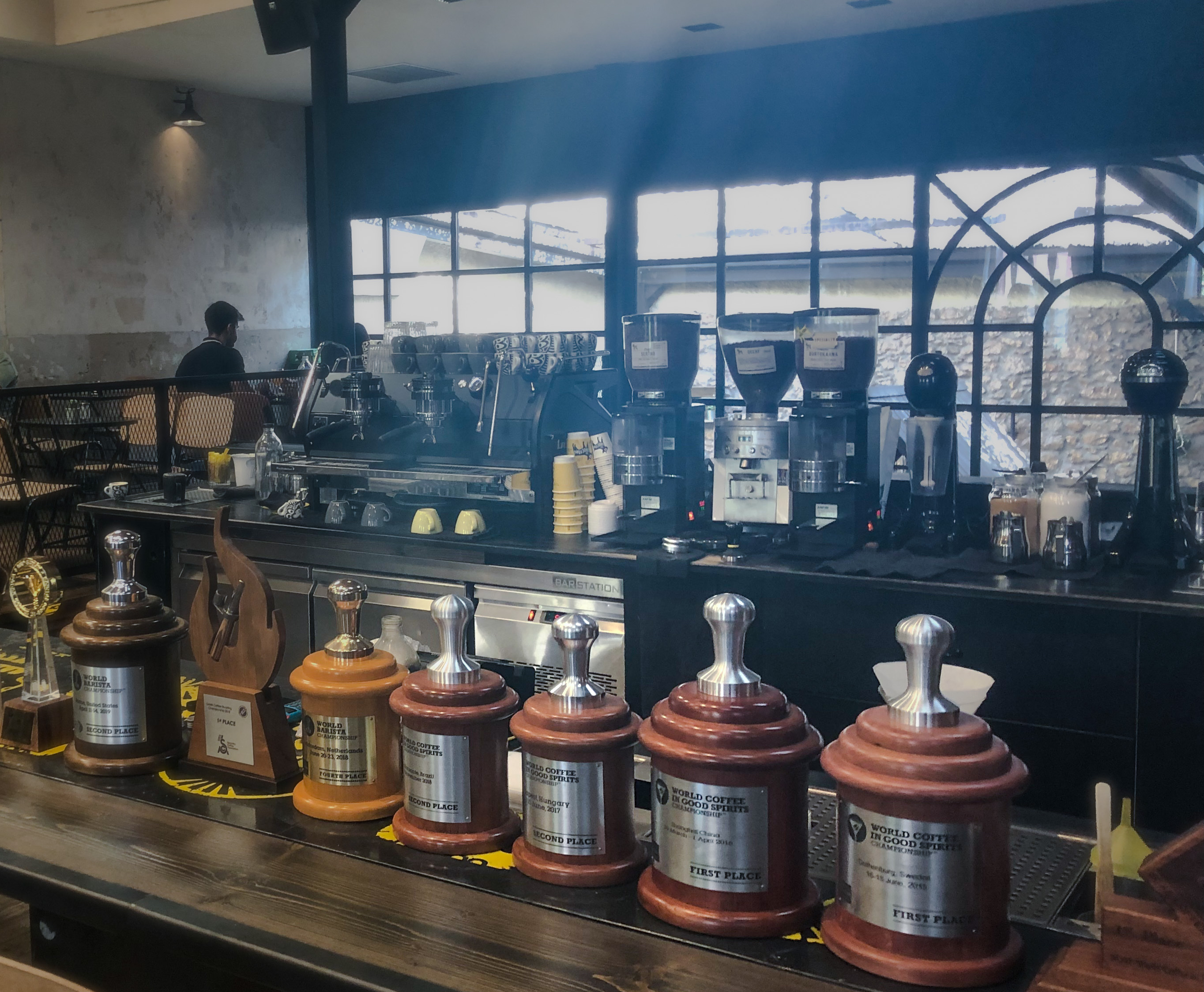 The barista bar at The Underdog with awards lining the countertop for their coffee and barista skills. A trendy cafe in Athens, Greece.