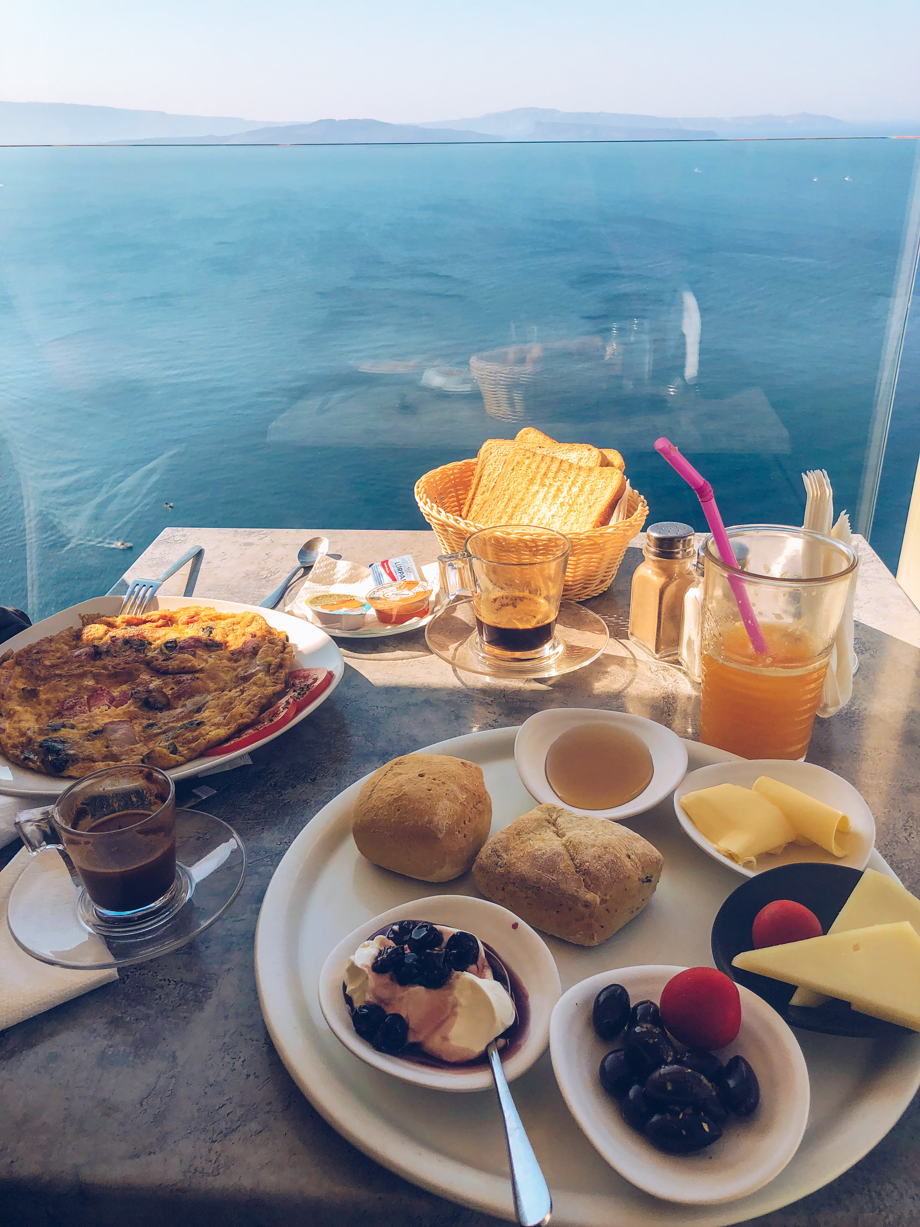 A table at Skiza Cafe with a traditional Greek breakfast, overlooking the caldera in Oia, Santorini.