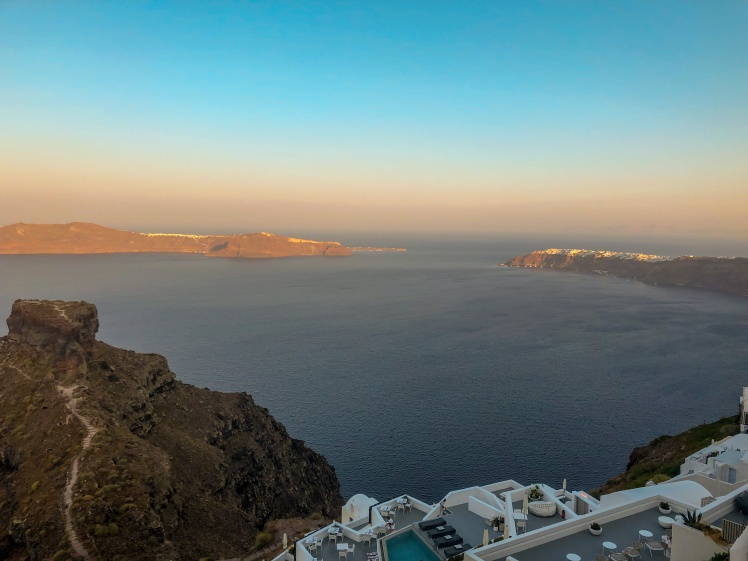 The view from the rooftop patio of Anita's Villa in Imerovigli, Santorini. The view includes Skaros Rock and the town of Oia in the distance.