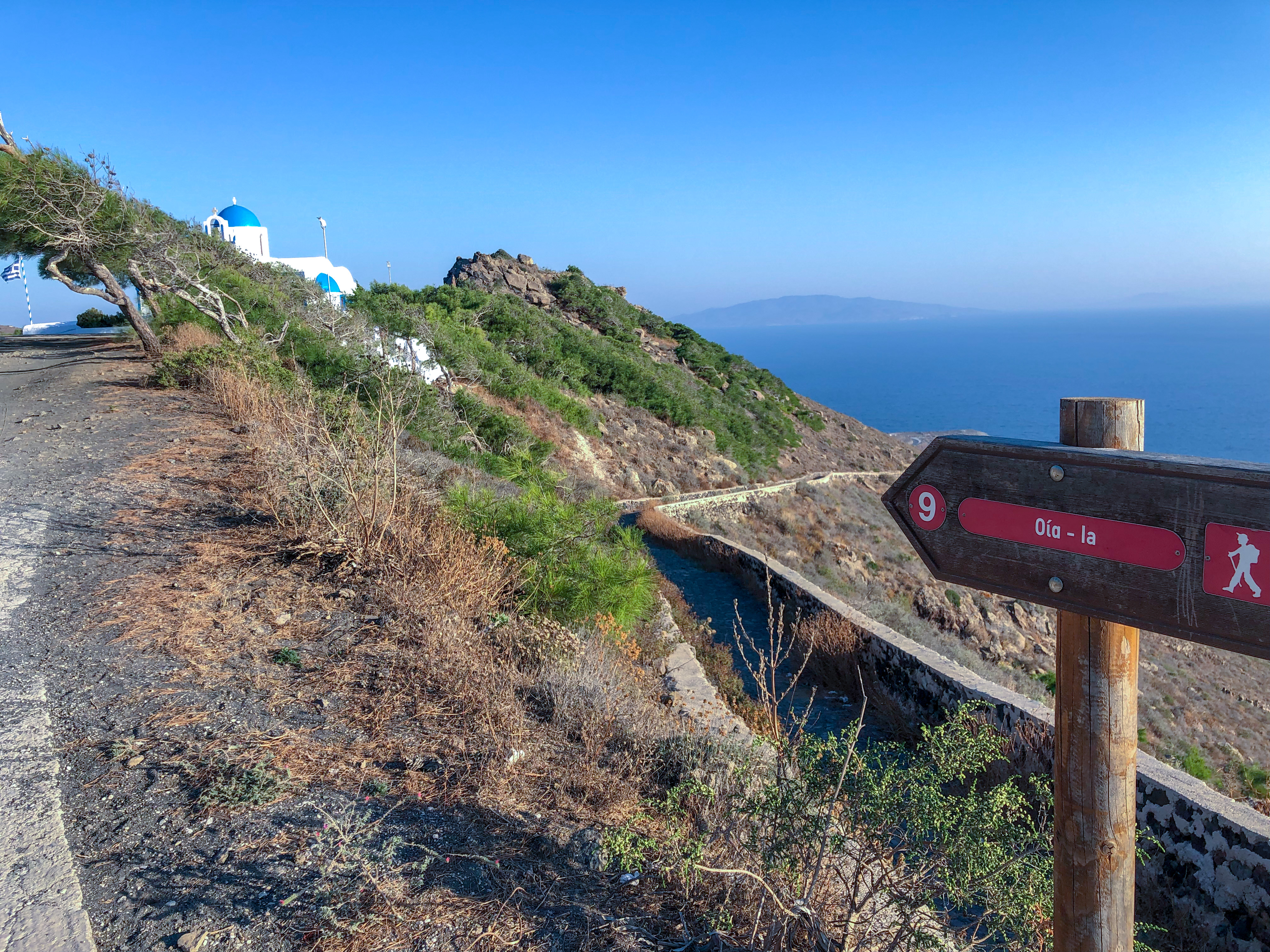 The trail sign that shows the direction for the Fira to Oia Hike, Santorini; a blue domed church can be seen in the distance.