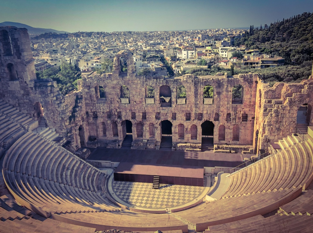 Odeon of Herodes Atticus, an ancient stone theatre, at the Acropolis with the city of Athens in the background.