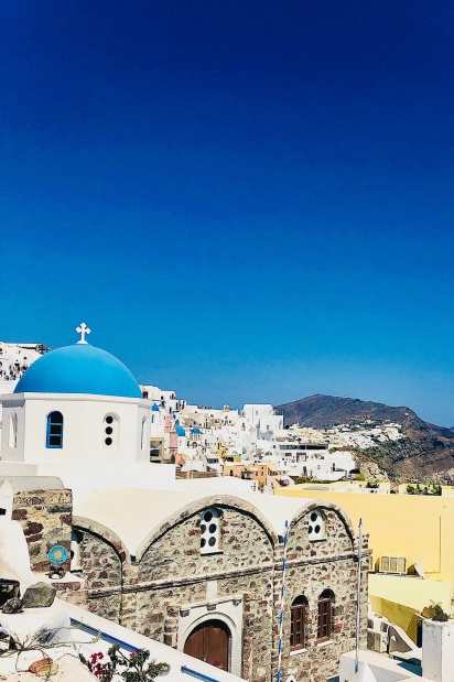 View of Santorini-Champagne with a blue domed church and whitewashed buildings built along the caldera cliffs.
