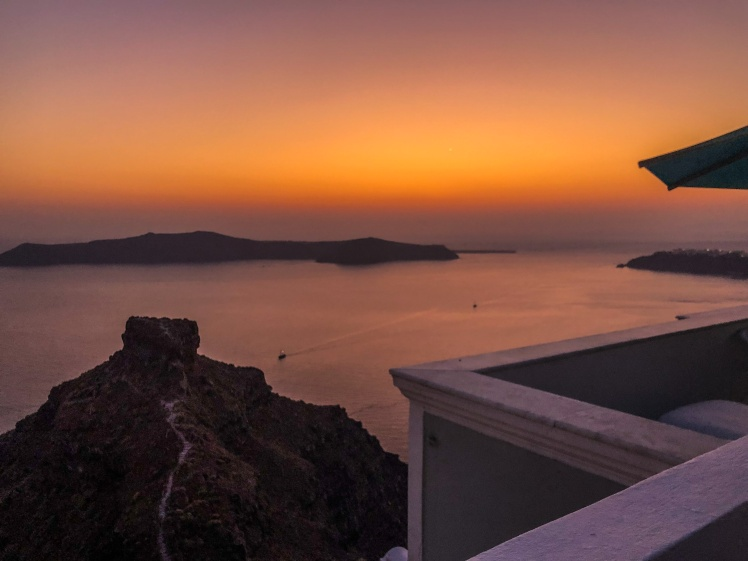 A sunset view from Anita's Villa in Santorini with Skaros Rock and Oia in the distance.