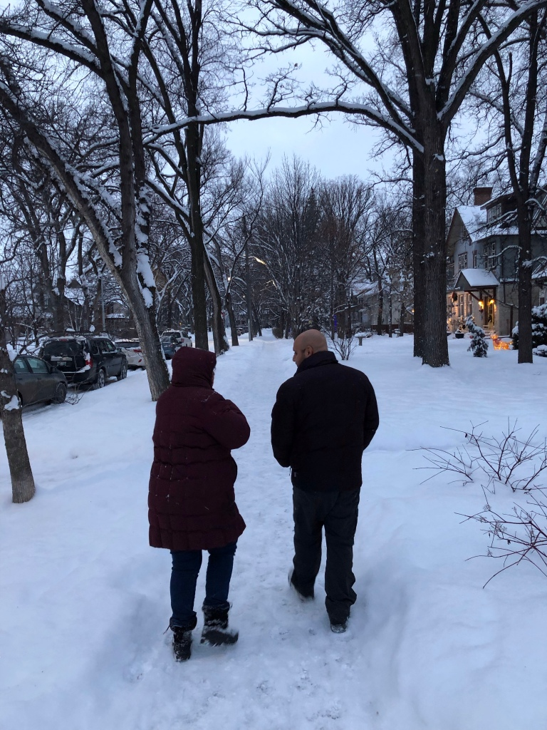 Two people walking down a residential street lined with character houses during a beautiful winter evening in Winnipeg, Manitoba.